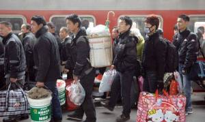 Passengers carrying their luggages prepare to get on the train in the railway station of Hangzhou, capital of east China's Zhejiang Province. China's Spring Festival falls on Feb. 3 this year. This year's holiday travel peak will be from Jan. 19 to Feb. 27. Some 230 million trips will be made on China's railway system during the period, up 12.5 percent year on year, according to estimates. Photo: Xinhua/Ju Huanzong