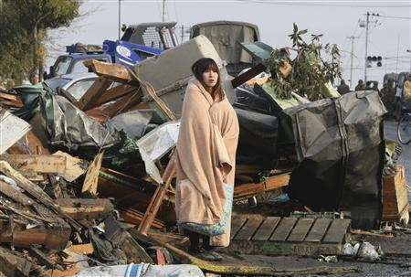 A woman looks at the damage caused by a tsunami and an earthquake in Ishimaki City, Miyagi Prefecture, after the magnitude 8.9 earthquake struck the area March 13, 2011. Photo: Reuters/Yomiuri Shimbun